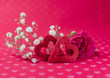 Red felt hearts with carnation and white flowers on heart patter Royalty Free Stock Photo