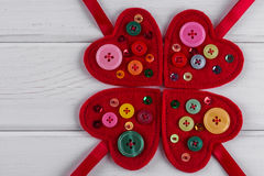 Red felt hearts crafts decorated with beads and buttons on white background. Royalty Free Stock Photography
