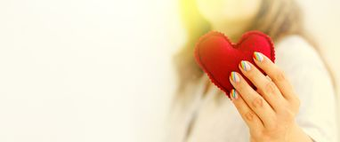 Red felted heart in femaile hands with rainbow manicure. Love, valentine, lgbt, pride concept Royalty Free Stock Photos