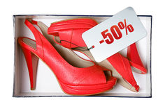 Red female shoes with price tag in box Royalty Free Stock Images