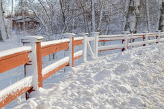 Red fence covered with snow, trees in the background Stock Photography
