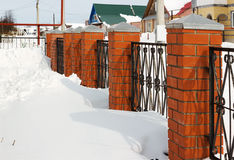 Red fence covered with snow Stock Photo