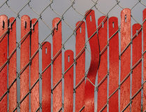 Red Fence Slipping. Vertical slats in a red fence are slipping earthward Stock Photo