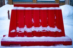 A red fence in snow on a street in winter stock photo