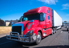 Red fency big rig semi truck modern trailer interstate highway. Modern bright red mod comfortable convenient hardy robust semi truck with dry van trailer on the Royalty Free Stock Image