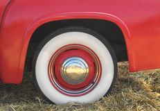 Red fender and whitewall tire. Close-up of a red fender with whitewall tire and chrome hubcap on a vintage pick-up truck Stock Images