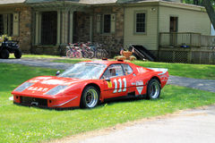 Red Ferrari racecar. Red Ferrari race car parked outdoors on lawn on a sunny day Royalty Free Stock Photo