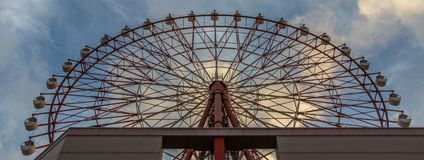 Red Ferris Wheel of Amu Plaza at JR Kagoshima Chuo Station against blue sky. Taken from the bottom. Located in Kagoshima, Kyushu, royalty free stock image