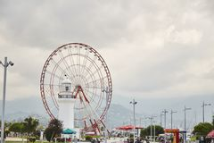 A red Ferris Wheel and a statue of a man and a woman. royalty free stock photo