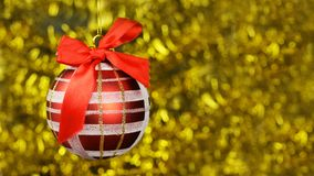 Red festive bright decor toy ball with a red bow and pattern. On a Christmas tree on a blurred background with a bokeh on a new year Royalty Free Stock Photo