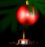 Red festive candle. Christmas tree, small burning candle and ball Stock Photography