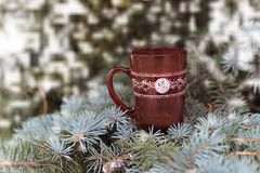 Red festive cup with a pattern with a hot drink. Near the Christmas tree for the new year Royalty Free Stock Photo