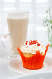 Red festive muffin and coffe Latte in a glass, on white wooden t Stock Photography