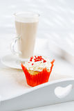 Red festive muffin and coffe Latte in a glass, on white wooden t Royalty Free Stock Image