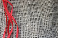 Red festive ribbons on the background texture of brown old canvas, linen natural material with a rough perpendicular interlacing o. F the fibers of the fabric stock photo