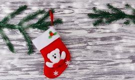 Red festive sock. santa claus boots. For gifts on a wooden background with a Christmas tree for the new year Stock Photos