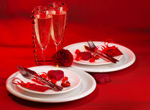 Red festive table setting. Photo of festive table setting, luxury white dishware on red tablecloth, hearts decorations, beautiful rose flower, two glasses for Stock Image