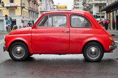 Red Fiat 500 under the rain. Old style Fiat 500 italian car in a rainy day. That famous car was the archetypal runabout and one of first city car in the early Stock Images