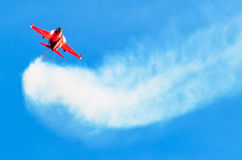 Red fighter jet in the blue sky with white smoke trail Royalty Free Stock Photos
