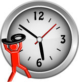 Red figure lifting the number 9 onto a clock face Stock Image