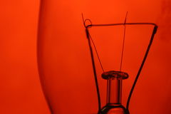Red filament. A close-up of a light bulb against a red background Royalty Free Stock Images