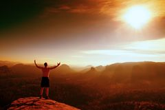Red filter photo. Naked climber in black pants  gesture of triumph. Tourist on peak of sandstone rock in national park Saxony Swit Royalty Free Stock Photo