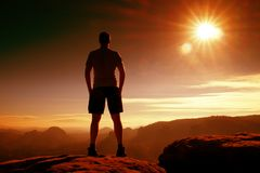 Red filter photo. Slim tourist in pants on the cliff of rock empire is watching down to valley. Hot Sun above. Royalty Free Stock Photo