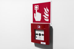 Red Fire alarm button. On white wall stock images