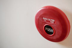 Red fire alarm and dirt on white wall background. Stock Photo