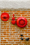 Red fire alarm sprinkler and hidrant in red brick wall Stock Photography