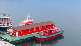 Red fire boat stand moored near floating fire station Stock Images