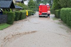 Fire department rushes to rescue when floods hit village in Europe after heavy rain. Red fire brigade engine,firefighting truck and firefighters rush to rescue royalty free stock images