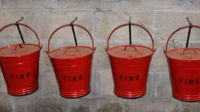 Red Fire Buckets Hanging on Wall royalty free stock photography