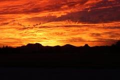 Red Fire Desert Arizona Hill Sunset. Gorgeous Red Fire Arizona Desert Sunset with Hills in foreground Stock Photo