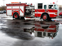 Red Fire Engine Parked in Street with Reflection Stock Photos