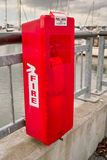 Red fire extinguisher. In box on dock railing royalty free stock photos