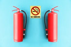 Red Fire extinguisher on the blue wall. Royalty Free Stock Photography