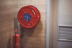 Red Fire Extinguisher Beside Hose Reel Inside the Room Royalty Free Stock Photography