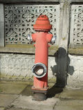 Red fire hydrant. Vintage red fire hydrant with an concrete wall background Stock Images