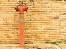 A red fire hydrant. On sidewalk in front of brick wall Royalty Free Stock Images