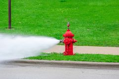 Red fire hydrant being flushed. Hydrant flushing - public works maintenance royalty free stock photography