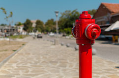 Red fire hydrant on blurred background. Red fire hydrant in the street on blurred background Stock Photo