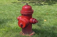 Red fire hydrant on a lawn. Bright red fire hydrant on the background of green grass Stock Photo