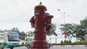 Red fire hydrant poles on street Ho Chi Minh city. Next to the road and passing cars and motorcycles. Vietnam. stock video footage