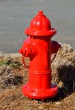 Red fire hydrant by road Stock Photo