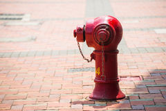 Red fire hydrant beside the road in town Royalty Free Stock Photo