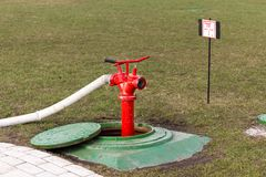 Red fire hydrant stands in manhole Stock Images