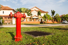Red fire hydrant at strategic residential ready for emergency. Red fire hydrant at strategic residential with residential house in background Royalty Free Stock Photography