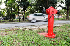 Red fire hydrant at strategic residential ready for emergency. Red fire hydrant at strategic residential road with care passing by in background Stock Images