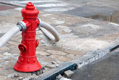 Red fire hydrant in use. With hoses connected Royalty Free Stock Photo